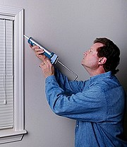 Applying caulking to stop drafty windows.